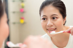 Closeup of healthy pretty woman looking mirror. Closeup photo of healthy pretty woman looking mirror reflection image smiling using toothbrush cleaning teeth in Royalty Free Stock Photo