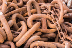 Closeup of heap of huge rusty chain links. Orkneys, Scotland - June 5, 2012: Closeup of heap of huge rusty heavy metal chain links on the pier of the Stromness royalty free stock image