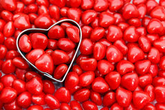 Red hot heart candies. Closeup of heart shaped cookie cutter surrounded by red hot candies Stock Images