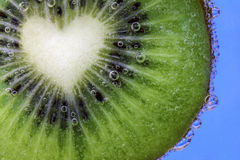 Closeup of a heart shaped kiwi slice covered in water bubbles Royalty Free Stock Image