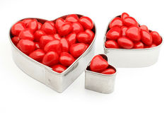 Red hot candies heart shaped tins. Closeup of heart shaped tins filled with red hot candies Stock Image