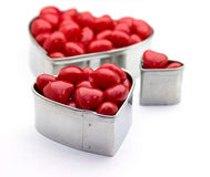 Red hot candies heart shaped tins. Closeup of heart shaped tins filled with red hot candies Royalty Free Stock Photos