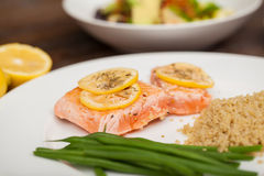 Closeup of a hearty dinner with salmon. Salmon served with some lemon and herbs next to some quinoa and green bean Stock Photo