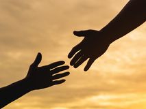 Closeup helping hands on the sunset sky background. Rescue & Hel. P Cencept stock photography