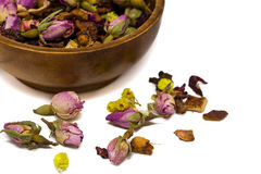 Closeup herbal rose tea in bowl isolated on white. Closeup image of herbal tea in a wooden bowl on white with some of the tea outside the bowl Royalty Free Stock Photos