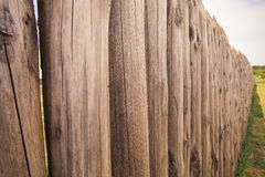 Closeup high old wooden fence of logs in form of palisade Royalty Free Stock Photo