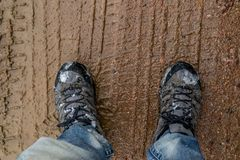 Hiking shoes standing in mud path stock photo