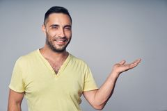 Closeup of hispanic man holding empty copy space for text or product on his palm. Closeup of casual hispanic man looking at camera holding empty copy space for royalty free stock image