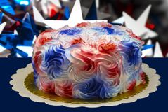 Closeup of a holiday cake with creamy sugary red white and blue swirls of icing sitting on a gold paper against a dark background stock photography