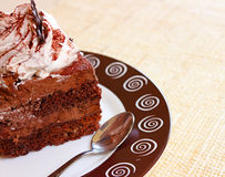 Closeup of home-made brown cake with white cream. Brown round plate Royalty Free Stock Photography