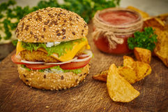 Closeup of home made burger. Fresh tasty burger with potato wedges and sauce on wooden table Royalty Free Stock Image