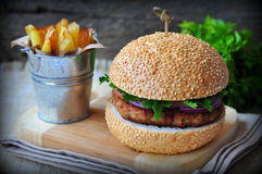 Closeup of home made burgers with the fried potato on wooden and linen background Stock Images