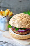 Closeup of home made burgers with the fried potato on wooden and linen background Stock Photos