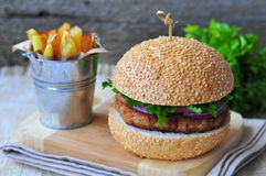 Closeup of home made burgers with the fried potato on wooden and linen background Royalty Free Stock Photography