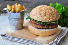 Closeup of home made burgers with the fried potato on wooden and linen background Stock Photography