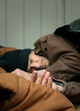 Closeup of Homeless Man Sleeping. Short depth of field closeup shot of homeless man asleep on the street. Hand is in focus...rest is gradually blurred Royalty Free Stock Images