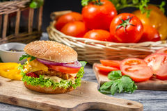 Closeup of homemade burger made from fresh vegetables. On old wooden table royalty free stock image