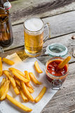 Closeup of homemade fresh fries with cold beer Royalty Free Stock Image