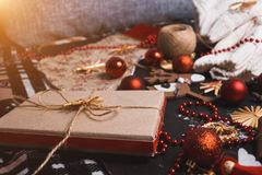 Closeup of a homemade gift box made of Kraft paper, red Christmas toys, b balls, beads on a black background royalty free stock photography