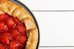 Closeup homemade pie with strawberries on white wooden table