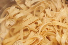 Closeup of homemade raw noodles from spelt dough cooking in boil Stock Photo