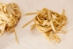 Closeup of homemade raw noodles from spelt dough on wooden table Stock Photo