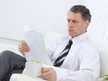 closeup Homme d'affaires lisant un document tout en se reposant dans une chaise dans la chambre d'hôtel Images stock