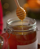 Closeup on honey flowing down from dipper in jar Stock Photography