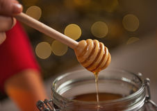 Closeup on honey flowing down from honey dipper in jar Stock Photo