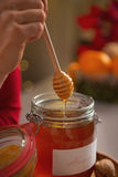 Closeup on honey flowing down from honey dipper in jar Stock Images