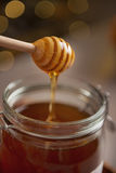 Closeup on honey flowing down from honey dipper in jar Stock Photos