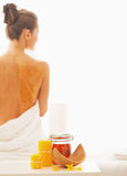 Closeup on honey spa therapy ingredients and woman in background Stock Photos