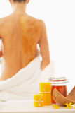 Closeup on honey spa therapy ingredients and woman in background Royalty Free Stock Photos