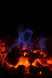 Closeup of hot red embers and blue flame in fireplace Royalty Free Stock Image