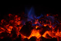 Closeup of hot red embers and blue flame in fireplace royalty free stock photography