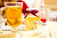 Closeup of hot tea, honey jar and pills on bedside table Stock Photos