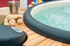 Closeup of hot tub. Detail view of luxury beautiful hot tub for relaxing, with decoration, towels, bottle of wine in nice interior stock photography