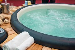 Closeup of hot tub. Detail view of luxury beautiful hot tub for relaxing, with decoration, towels, bottle of wine in nice interior stock photos