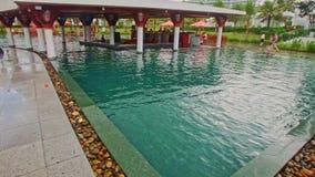 Closeup Hotel Swimming Pool Pavilion in Middle Sun Umbrellas. NHA TRANG/VIETNAM - OCTOBER 21 2016: Close view hotel swimming pool with pavilion in blue water stock video