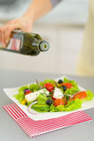 Closeup on housewife adding olive oil in salad Stock Photos