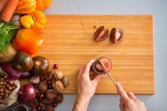 Closeup on housewife cutting purple tomato Royalty Free Stock Photos