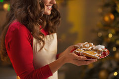 Closeup on housewife enjoying with plate of christmas cookies Stock Photos