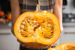 Closeup on housewife in kitchen showing pumpkin Royalty Free Stock Photos