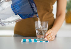 Closeup on housewife pouring water into glass Royalty Free Stock Photo