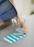 Closeup on housewife pouring water into glass Royalty Free Stock Photos