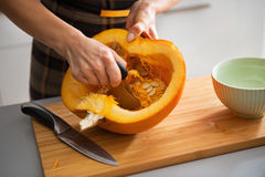 Closeup on housewife removing filling from pumpkin Stock Photography