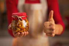Closeup on housewife showing jar with honey nuts and thumbs up Stock Photo