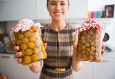 Closeup on housewife showing jars with compote royalty free stock images