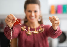 Closeup on housewife showing mushrooms on string Royalty Free Stock Photography