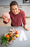 Closeup on housewife showing piggy bank. Closeup on happy young housewife showing piggy bank after local market shopping Stock Images